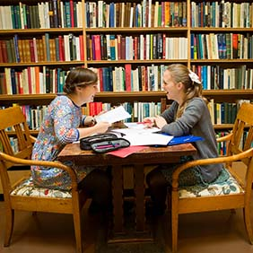 Two students laughing and studying together around a desk in front of book shelves.