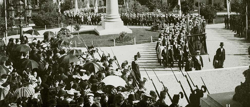 Photo from 1893. Students with flags in procession through the university park towards the university building past the statue of Erik Gustaf Geijer.