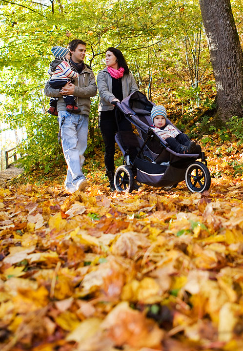 a family with two children and stroller walks in a park