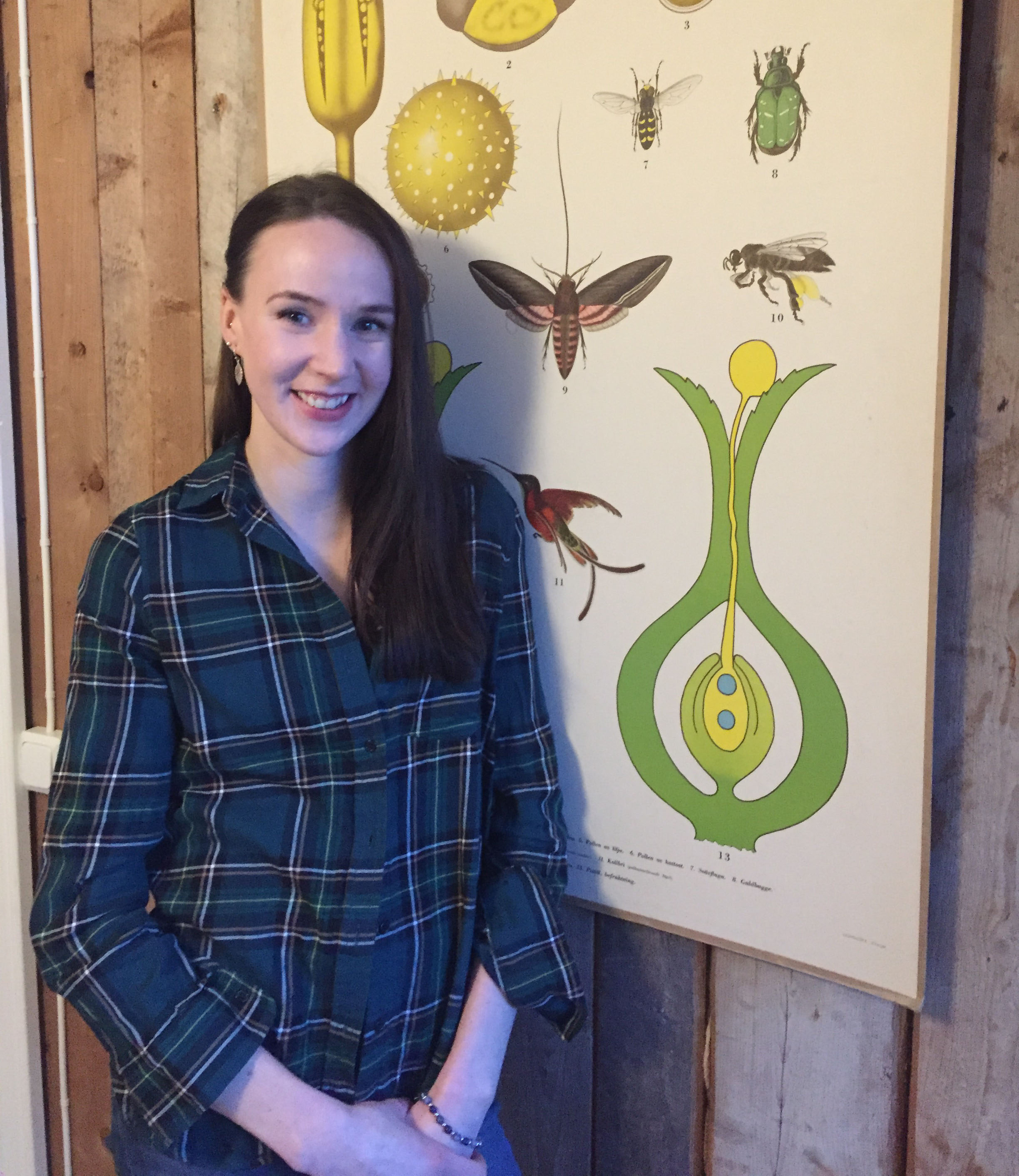 Photo of alumna Annie Hammare standing in front of a poster showing illustrated insects