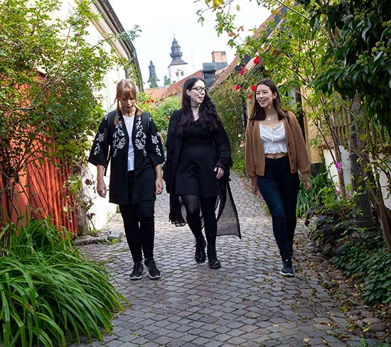 3 students walking on a cozy and narrow street in Visby