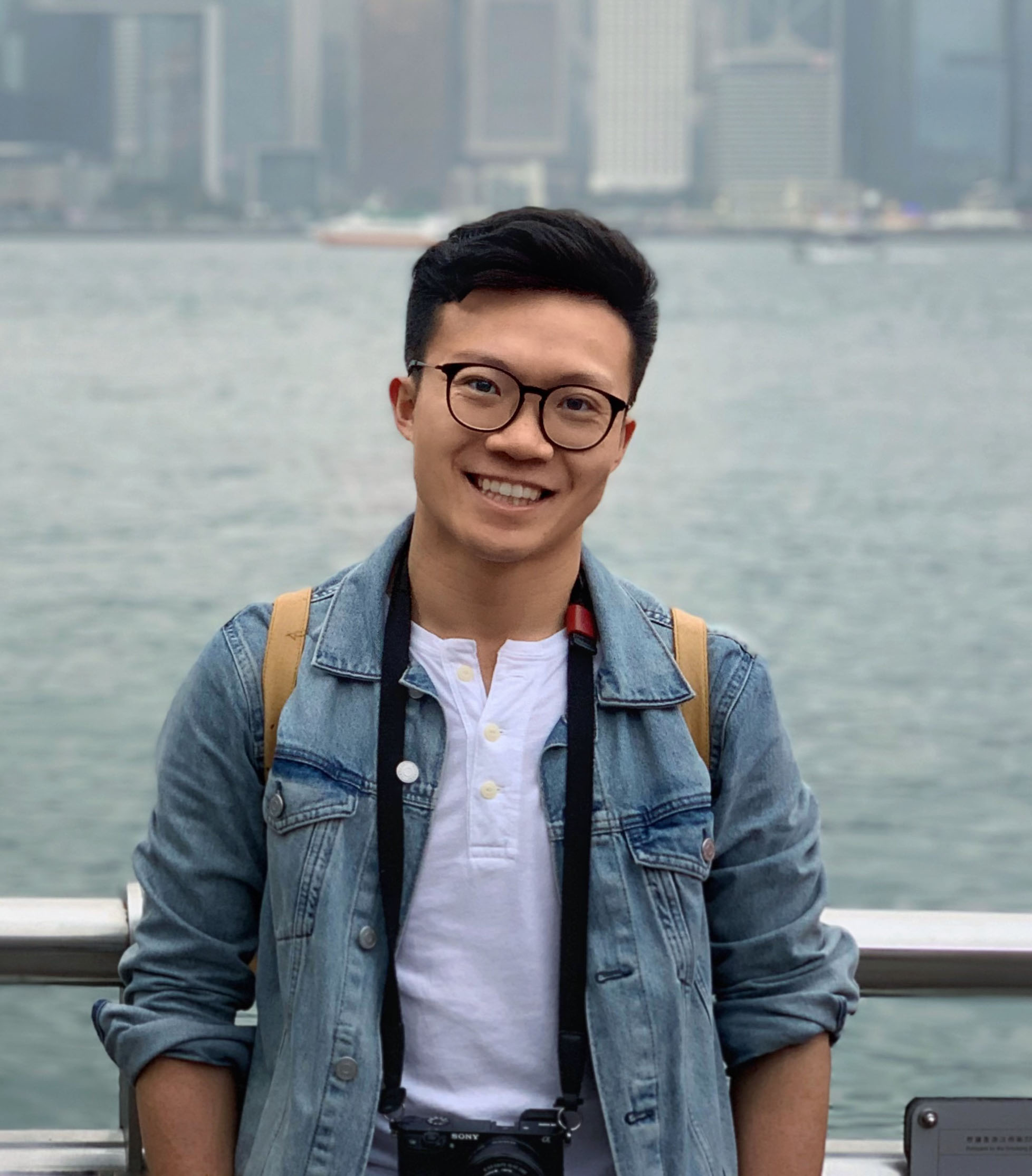 Photo of alumnus Jiawei Xu standing in front of the Victoria harbour in Hong Kong