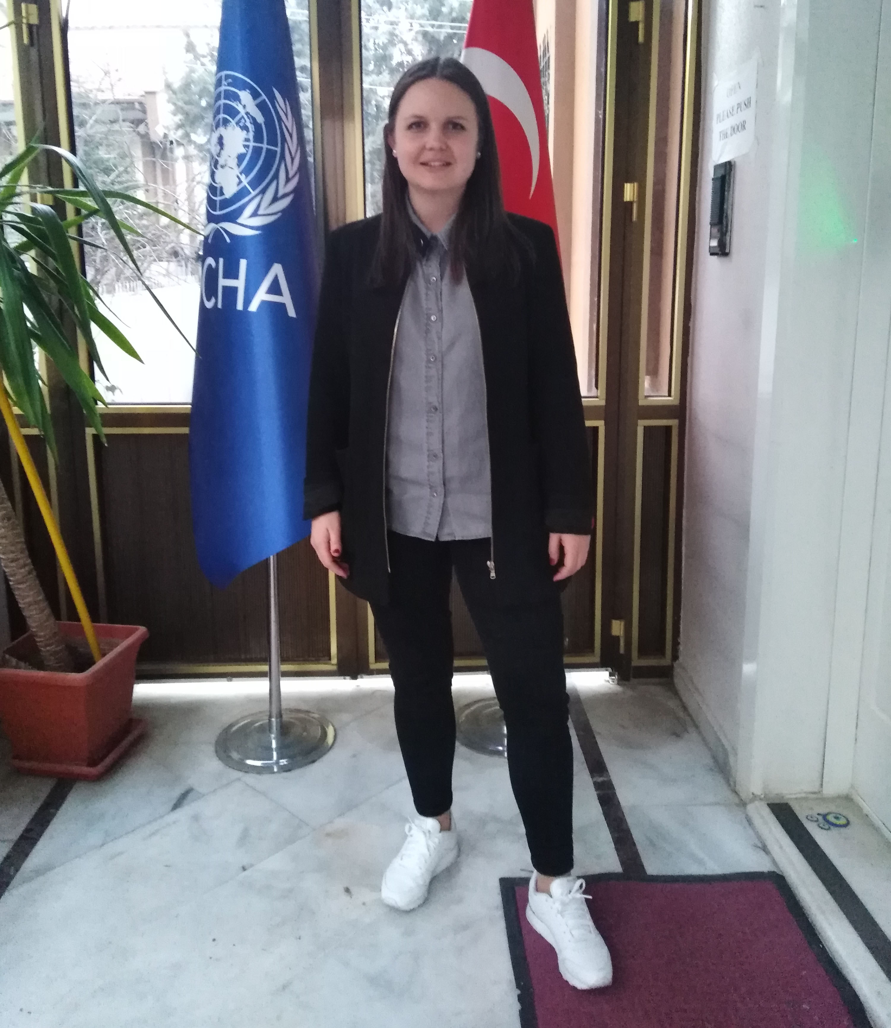 Photo of Rebecca Lindqvist standing in front of the flags of UN OCHA and Turkey