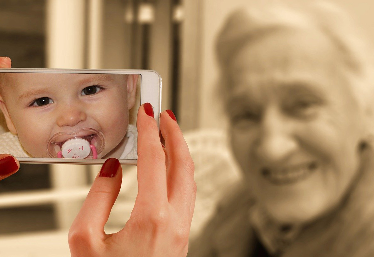 Picture of hands holding a mobile phone with photo of baby and old lady in the background